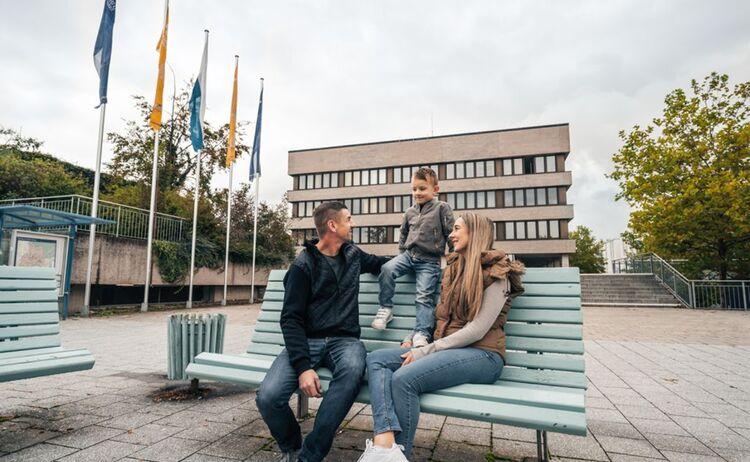 Eine dreiköpfige Familie sitzt auf einer Bank vor dem Rathaus und unterhält sich: Klick öffnet eine vergrößerte Ansicht