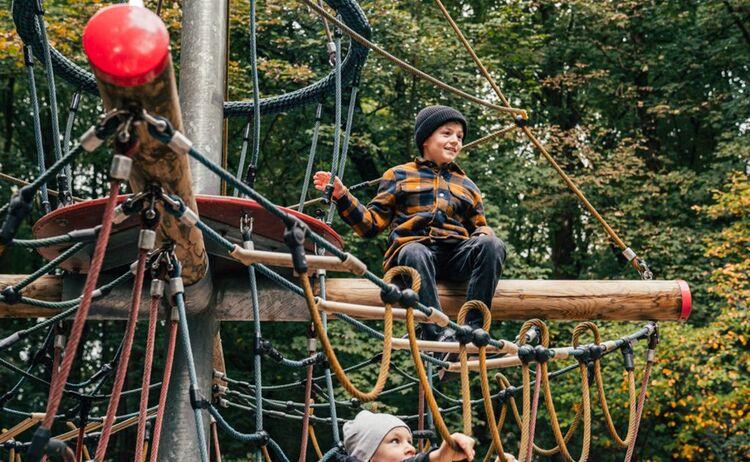 Zwei Jungs klettern auf einem Klettergerüst auf dem Spielplatz: Klick öffnet eine vergrößerte Ansicht