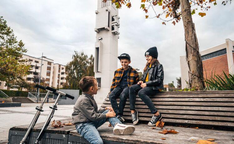 Zwei Jungen und ein Mädchen sitzen am Sartrouville Platz auf einer Bank und unterhalten sich. : Klick öffnet eine vergrößerte Ansicht