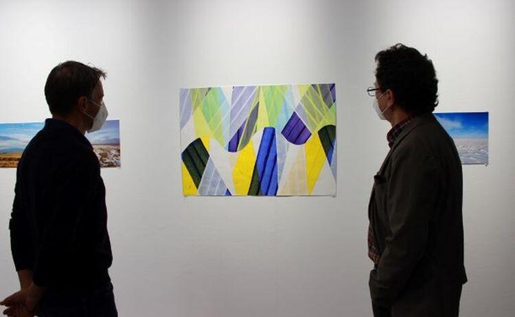 Zwei Besucher betrachten eine farbige Papierarbeit: Klick öffnet eine vergrößerte Ansicht