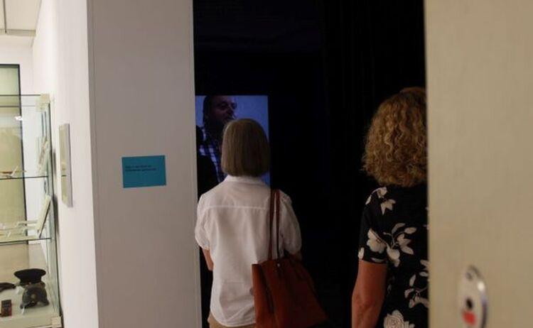 Besucher schauen einen Film zur Ausstellung: Klick öffnet eine vergrößerte Ansicht