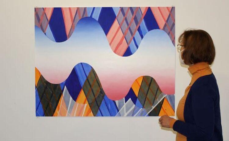 Besucherin betrachtet farbige Papierarbeit: Klick öffnet eine vergrößerte Ansicht