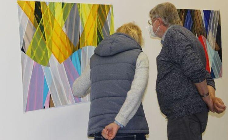 Gäste betrachten farbenprächtige Papierarbeit: Klick öffnet eine vergrößerte Ansicht