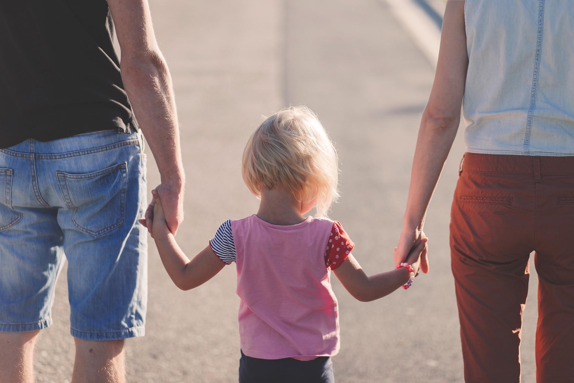 Symbolbild Vereinbarkeit Familie und Beruf, das ein kleines Kind mit seinen Eltern Hand in Hand zeigt