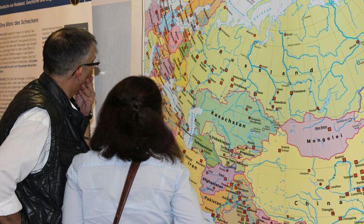 Zwei Besucher betrachten eine Landkarte der Ausstellung Deutsche aus Russland: Klick öffnet eine vergrößerte Ansicht