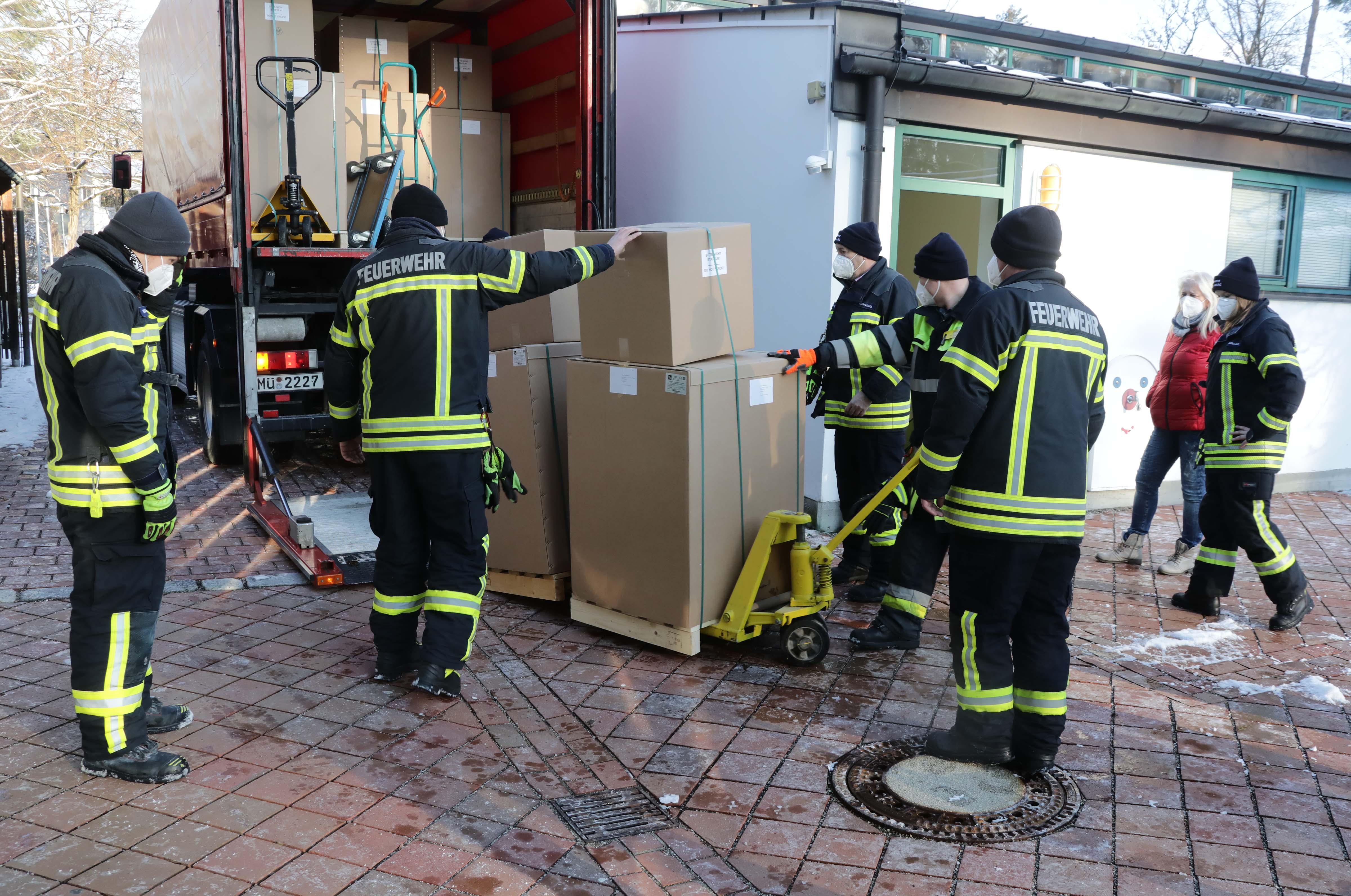 Mitglieder der Freiwilligen Feuerwehr Waldkraiburg bringen die Lieferung der Luftfiltergeräte zum LKW