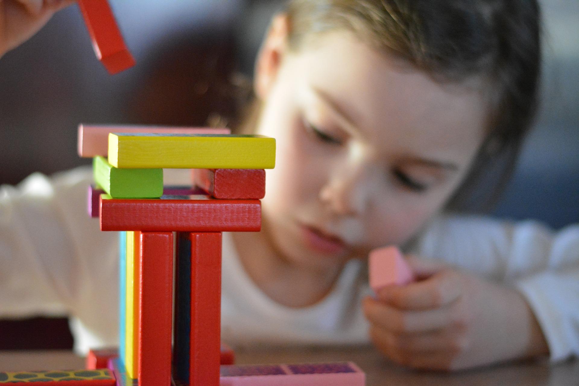 Ein Mädchen spielt mit Bauklötzen im Kindergarten