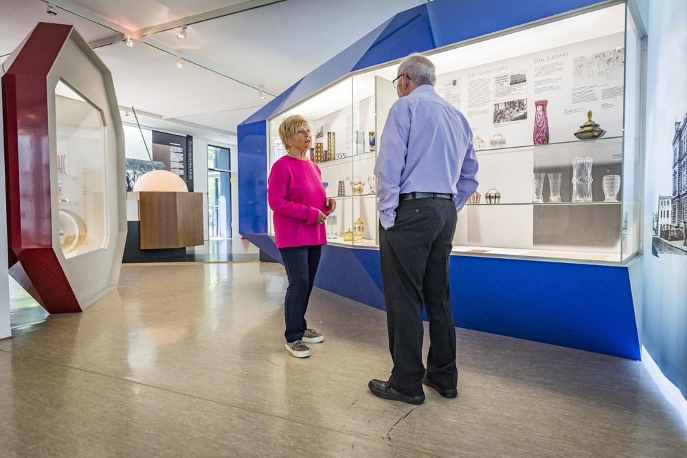 Zwei Besucher sehen sich die Exponate im Glasmuseum an
