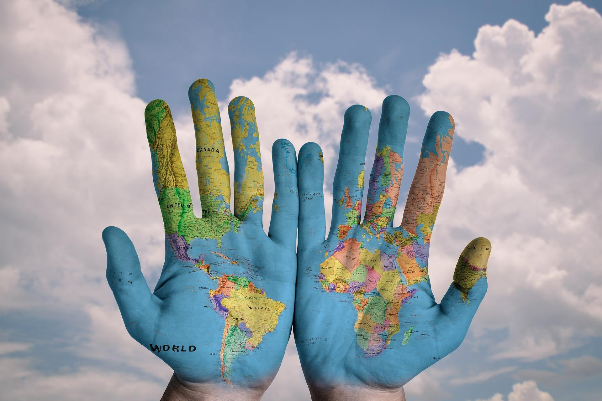 Symboldbild Asyl, das zwei Hände zeigt, auf die eine Weltkarte aufgezeichnet ist