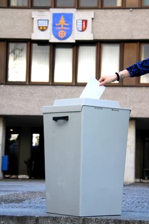 Symbolbild Wahl, das eine Wahlurne vor dem Rathaus zeigt in die ein Stimmzettel eingeworfen wird