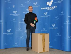 Erster Bürgermeister Robert Pötzsch hält eine der CO2-Ampeln in der Hand