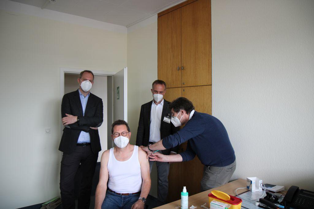 Johann Vetter Mitglieder der Geschäftsleitung der Firma Netzsch lässt sich von Betriebsarzt Dr. Hiermer mit Astra Zeneca impfen. Geschäftsführer Jens Heidkötter und Erster Bürgermeister Robert Pötzsch machen sich selbst ein Bild von der Impfaktion