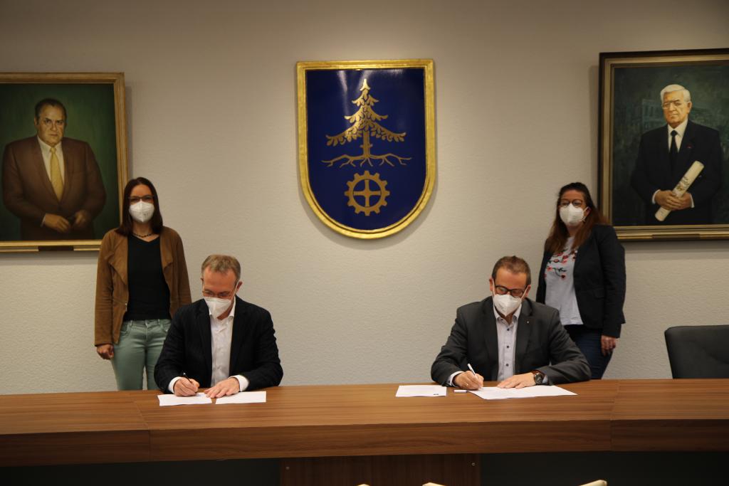 Bürgermeister Robert Pötzsch unterzeichnet gemeinsam mit Caritas-Kreisgeschäftsführer Richard Stefke die Kooperationsvereinbarung. Die beiden Caritas-Mitarbeiterinnen Maria Irl und Nicole Skrojek stehen im Hintergrund