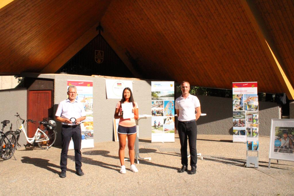 Der Schulleiter des Waldkraiburger Gymnasiums Helmut Wittmann und Schülerin Carmen Hansmaier nehmen den Preis für den ersten Platz bei der Schulwertung von Bürgermeister Robert Pötzsch entgegen.