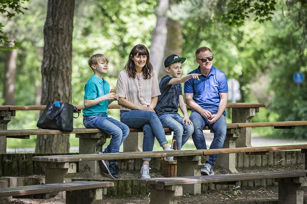 Eine Familie sitzt im Stadtpark auf der Tribüne vor dem Pavillion