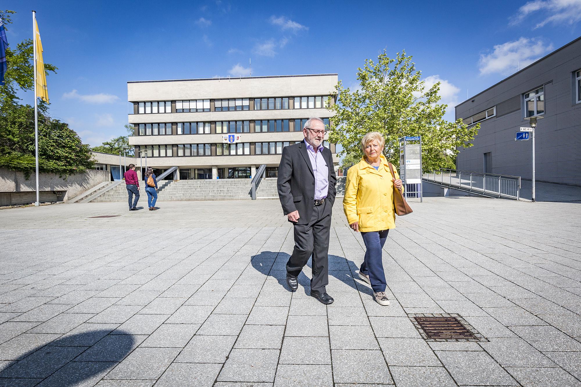 Zwei Senioren spazieren am Rathaus Vorplatz