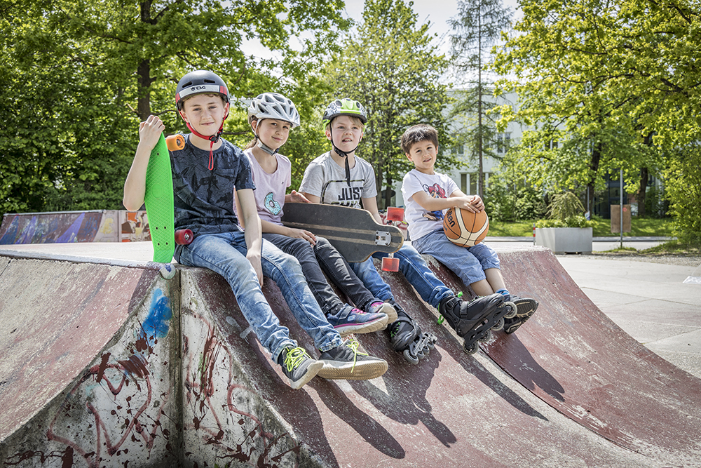 Vier Kinder sitzen auf mit ihren Skateboards auf einer Bahn im Skaterpark