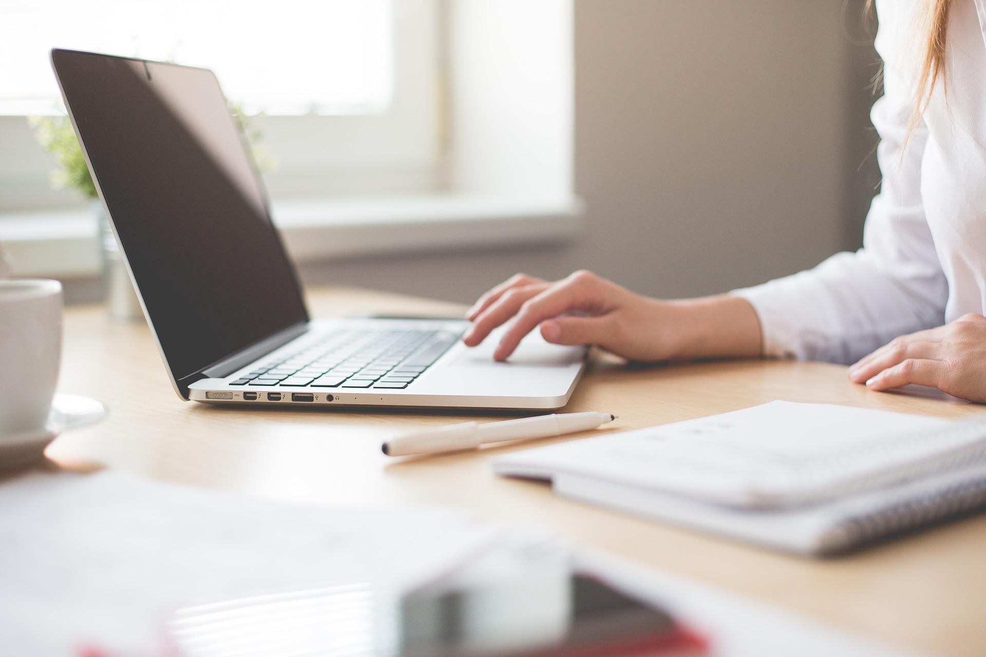 Symboldbild Home Office, das eine Frau an einem Laptop beim Arbeiten zeigt