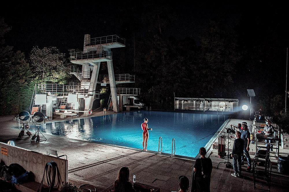 Aufnahme der Dreharbeiten zum Kinofilm Beckenrad Sheriff Waldbad, eine Frau steht im Badeanzug am Sprungturmbecken